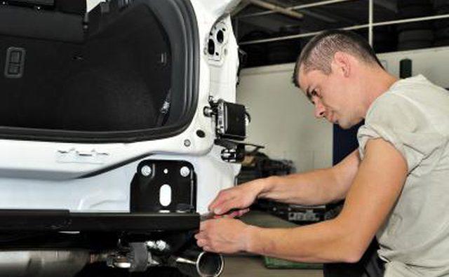 Механик собирает прицепное устройство