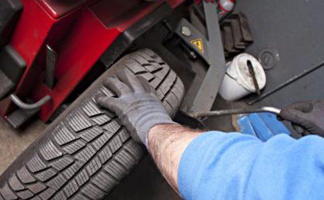 Механик, ремонтирующий выравнивание автомобиля.